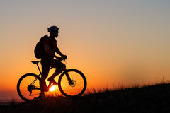 Silhouette man stand with mountain bike on the meadow stock photography