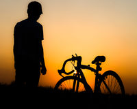 Silhouette of a man. Silhouette, man standing with bike Stock Image