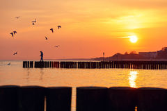 Silhouette of a man standing on a breakwater Stock Images