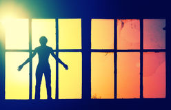 Silhouette of man standing in broken window abandoned building royalty free stock photos