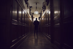 Silhouette of man standing in dark corridor in an old house. stock image