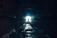 Silhouette of man standing in dark underground corridor. Light at end of tunnel concept. Toned Royalty Free Stock Images