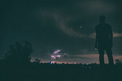 Silhouette of Man Standing Distance Trees during Night Time Stock Images