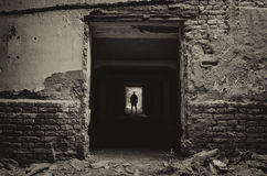 Silhouette of man standing at the end of dark corridor Stock Images
