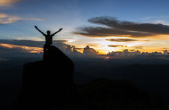 Silhouette man standing on giant rock and spreading hand on moun. Tain top at sunset Royalty Free Stock Photos