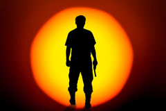 Silhouette man standing hand holding gun revolvers on bi Royalty Free Stock Images