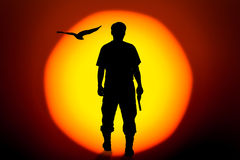 Silhouette man standing hand holding gun revolvers on bi. Silhouette rear of man standing hand holding gun revolvers on big sunset background Royalty Free Stock Images