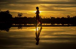 Silhouette of Man Standing on Lake at Sunset Royalty Free Stock Images