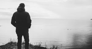 Silhouette of Man Standing Near Body of Water royalty free stock image