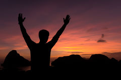 Silhouette of man standing and open arms raised towards sky con Stock Photography