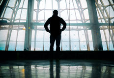 Silhouette of man standing over window. Silhouette of man standing back over big window Royalty Free Stock Images