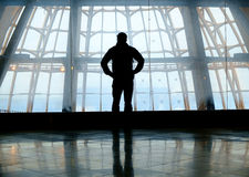 Silhouette of man standing over window. Silhouette of man standing back over big window Stock Image