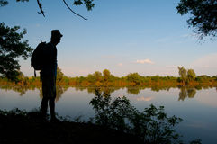 Silhouette of the man standing on the river shore stock images