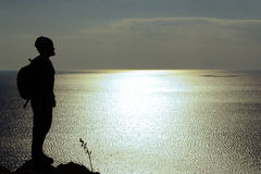 Silhouette of man standing on a rock and looking at sea. Silhouette of man with backpack standing on a rock and looking at blue Royalty Free Stock Images