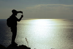 Silhouette of man standing on a rock and looking at sea. Silhouette of man with backpack standing on a rock, looking at blue sea and taking photo by his smart Royalty Free Stock Photos
