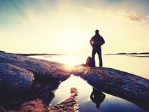 Silhouette of man standing on a rock and looking toward the evening sun. Silhouette of man standing on a rock and looking over sea toward the evening sun Stock Photos