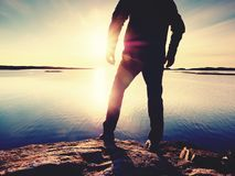 Silhouette of man standing on a rock and looking toward the evening sun. Silhouette of man standing on a rock and looking over sea toward the evening sun Stock Photography