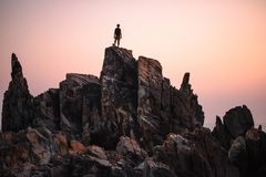 Silhouette of man standing on the rock. Man stands on the peak of rock and watching to sundown. Beautiful moment the miracle of nature royalty free stock photography