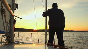 Silhouette of man standing on sailing yacht and watching sunset stock footage