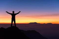 Silhouette of man standing and spread hand on the top of mountai Royalty Free Stock Image