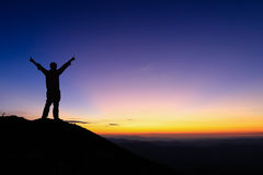 Silhouette of man is standing and spread hand on top of mountain Stock Photos