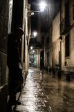 Silhouette of a man standing on the street at gothic quarter in Barcelona at rainy night, depression and loneliness Royalty Free Stock Photos