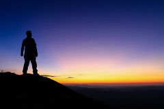 Silhouette of man standing on the top of mountain to enjoy colou Royalty Free Stock Images