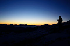 Silhouette of man standing on the top of mountain to enjoy colourful sky. Stock Photos