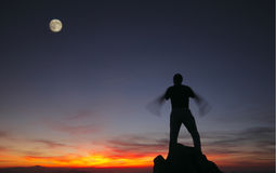 Silhouette of a man standing on the top at sunset Stock Images