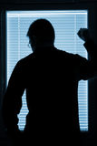 Silhouette of a man standing by the window Stock Photo
