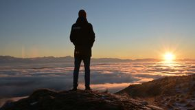 The silhouette of a man stands at sunset above the clouds and contemplates the setting sun. The concept of tranquility. And pleasure in traveling stock footage