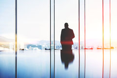 Silhouette of a man successful lawyer is thinking about the future of an important court session. Male CEO is standing in modern office interior near big window stock images