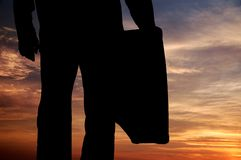 Silhouette of man with suitcase. Stock Images