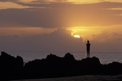 Silhouette of man at sunset over ocean, Tobago. Sunset at Black Rock Beach in Tobago, West Indies Royalty Free Stock Photo