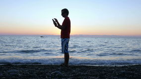 Silhouette of a man at sunset passes along the waterfront with a tablet computer. He stops, check the message and moves stock video