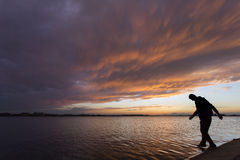 Silhouette of a man at sunset walking on water Stock Images
