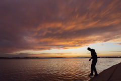 Silhouette of a man at sunset walking on water Royalty Free Stock Photos