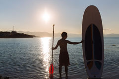 Silhouette of man with sup surf and paddle in hands at the ocean. Concept lifestyle, sport Royalty Free Stock Photos
