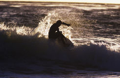 Silhouette Man Surfing Wave. Side view of a silhouette man surfing wave Royalty Free Stock Photo