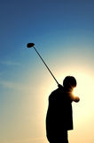 Silhouette of a Man Swinging a Golf Club. Silhouette of a Man Swinging a Golf Driver with Sun in the SKy Stock Images