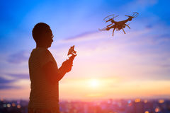 Silhouette of man take drone. Silhouette of man play drone in the sunset, asian Stock Photos