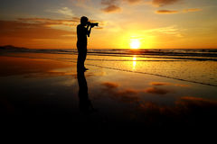 Silhouette man take picture on sunset background Royalty Free Stock Images