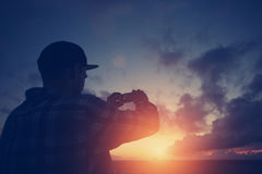 Silhouette of man taking photo of sunset with mobile phone Stock Photos