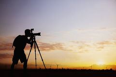 Silhouette of man taking photos with his camera at sunset with a dramatic sky Royalty Free Stock Photo