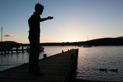 Silhouette of man taking picture with mobile phone. Picture taken from Ambleside Marina across Lake Windermere, Lake District, UK Stock Photography