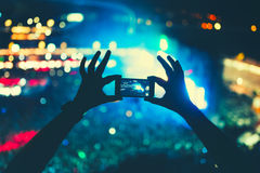Silhouette of a man taking pictures at festival concert. Concert lights and performance by artists. Stock Images