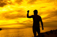 Silhouette of man with their hands in the sunset Stock Photo