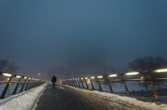 Silhouette of a man in a thick fog at night. Silhouette of a man passing through a pedestrian bridge in the dark in a strong fog. Handrails with integrated lamps stock image