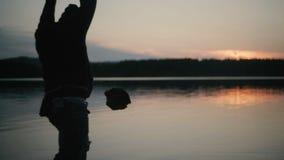 Silhouette man throwing large stone at lake sunset stock video footage