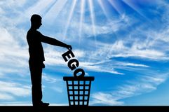 Silhouette of a man throws the word ego into the garbage bin stock photo